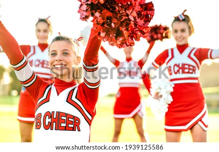 Group of female cheerleaders performing outdoors at university campus - Sport concept of cheerleading team training at high school during sunset - Warm backlight filter with focus on left girl eyes ストックフォト ©