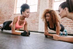 Group of female doing pushups together in gym. Three young women exercising in healthclub.
