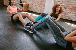 Group of female exercising in healthclub. Three young woman doing situps together in gym.