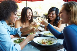Group Of Female Friends Enjoying Meal At Outdoor Restaurant