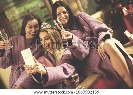 group of female friends in spa have fun and making selfie photo with mobile phone, celebrate bachelorette party