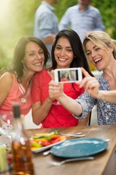 Group of female friends in their thirties taking a selfie during a party on a terrace. In the background a beautiful garden where their men doing a bbq. Shot with flare