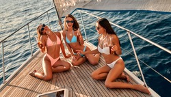 Group of female friends relaxing on luxury yacht. Three beautiful girls in swimsuits sitting on yacht deck,drinking beer and having fun together while sailing in the sea.Traveling and yachting concept