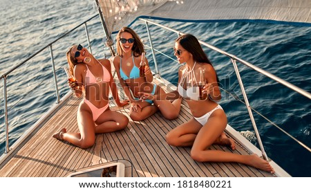 Group of female friends relaxing on luxury yacht. Three beautiful girls in swimsuits sitting on yacht deck,drinking beer and having fun together while sailing in the sea.Traveling and yachting concept Foto stock ©