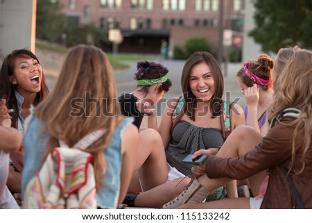 Group of female students sitting outside laughing together