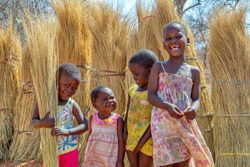 Group of few happy girls and a boy playing with the thatching grass in a village in Botswana