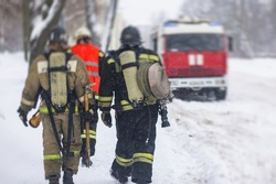 Group of fire men in uniform, firefighters with the fire engine truck fighting vehicle in the background, winter streets