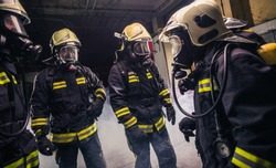 Group of firefighters in the fire department checking their gas mask equipment