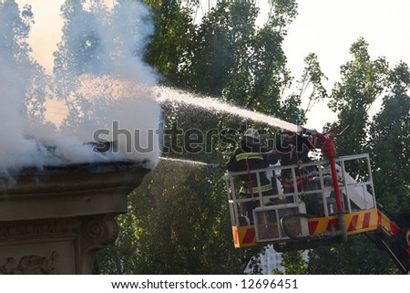 group of firefighters spraying water on fire and smoke
