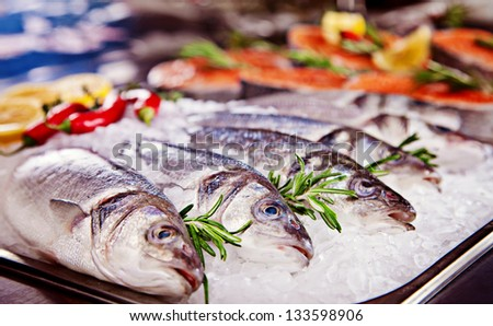 Group of fish served on ice with rosemary