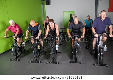Group of fit mature adults in a spinning class