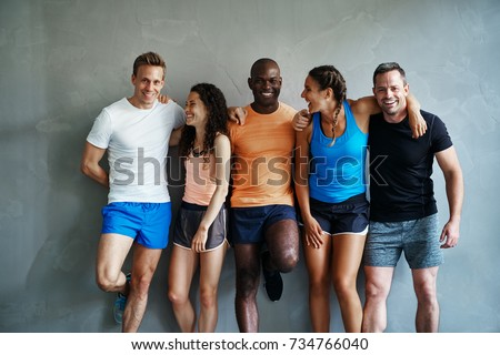 Group of fit young friends in sportswear laughing while standing arm in arm together in a gym after a workout