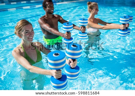 Group of  fit young people doing aqua fitness exercise with plastic dumbbells in swimming pool on summer sunny day outdoors