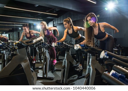 Group of fitness girls riding exercise bikes together on cycling class at gym.