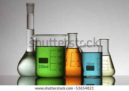 group of five beakers containing colored liquid