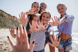 Group of five fashion kids enjoing their time in shallow water. The children wearing jeans clothing and swimsuits. Friends holding hands and walking at the beach. A lot of hands