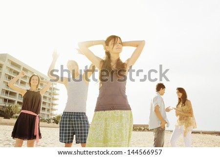Group of five friends dancing, listening to music and having fun on an urban beach in the city with their arms up against the sunshine filtering trough them.