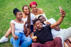 group of five friends female and male taking selfie on camera smartphone and having fun outdoors lifestyle near lake,eating burger picnic in the park