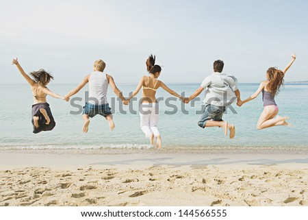 Group of five friends holding hands and jumping at once on the shore of a golden sand beach against a blue sea and sky, expressing energy, fun and joy during their summer vacation.