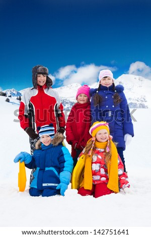 Group of five friends kids boys and girls standing together outside in snow