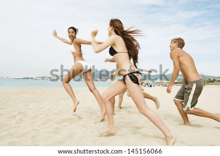 Group of five friends running together towards the sea water shore, being spontaneous and having fun while on a summer vacation on a beach showing happy expressions.