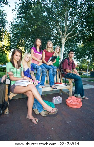Group of five frowning high school girls and one boy sitting on a bench holding books. Vertically framed photo.
