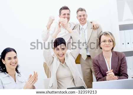 Group of five happy business people smiling and clapping, celebrating business success.
