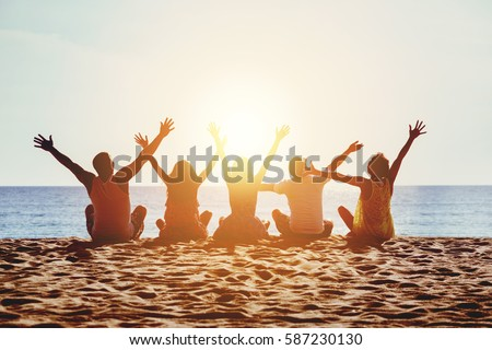 Group of five happy people sits on background of empty sunset beach. Travel or sea vacations concept