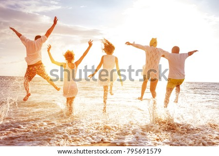 Group of five happy peoples run and jump to sea beach against sunset sun