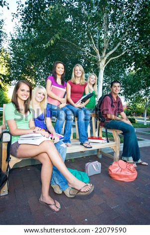 Group of five high school girls and one boy sitting on a bench holding books. Vertically framed photo.