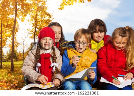 Group of five kids around 10 years old drawing images sitting outside in autumn day