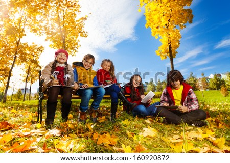 Group of five kids, friends, boys and girls, sitting on the bench in autumn park on sunny day and draw pictures