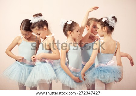 Group of five little ballerinas posing together and practicing for performance. They are good friend and amazing dance performers