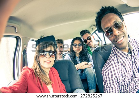 Group of five people driving to vacation and taking a selfie in the car - Happy people of of diverse ethnics in an automobile - Friends renting a car and driving somewhere