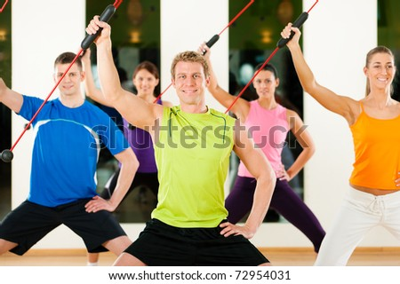 Group of five people exercising with a bar to strengthen the intrinsic muscles in gym or fitness club