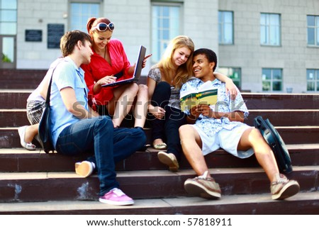 Group of five students outside sitting on steps - stock photo