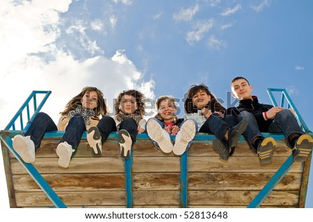 Group of five teenage friends sitting together with their legs hanging down on you