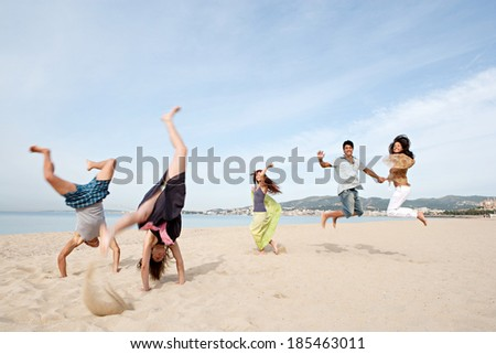 Group of five teenagers friends enjoying a day on the beach together, jumping and doing cartwheels celebrating the summer holidays during a sunny day with a blue sky. Outdoors teenagers lifestyle.