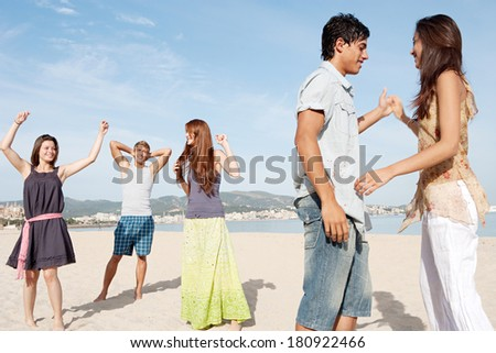 Group of five teenagers friends enjoying a day on the beach together, listening to music and dancing, celebrating the summer holidays during a sunny day with a blue sky.