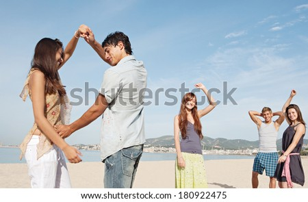 Group of five teenagers tourists friends enjoying a day on the beach together, listening to music and dancing, celebrating the summer holidays during a sunny day with a blue sky.