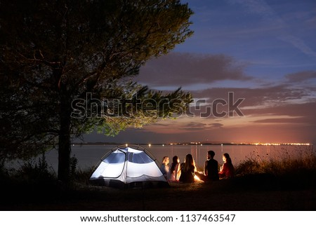 Group of five travellers, girls and boy having a rest on lake shore under tree around campfire at tourist tent on quiet water surface and blue evening sky background. Tourism and camping concept. #1137463547