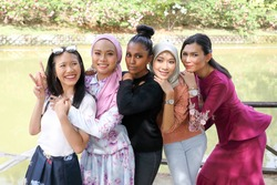 group of five woman Malay Chinese Indian Asian Malaysian outdoor green park lake nature stand talk mingle hand on friends shoulder