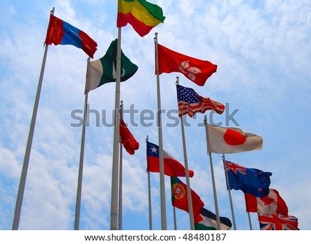 Group of flags against cloudy sky
