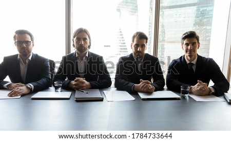Group of focused male professional headhunters recruiters sitting at table, waiting for job candidate for interview. Serious hr managers teammates in formal wear looking at camera, hiring process.