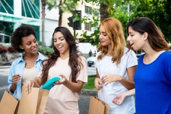 Group of four beautiful women shopping clothes in the city