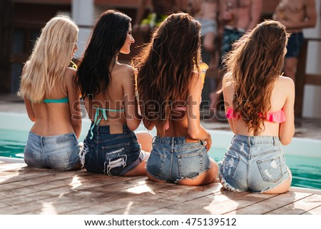 Group of four beautiful young women with long hair in jeans shorts sitting near swimming pool