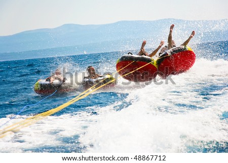 Group of four bouncing up over wake on tubes on Croatian coast