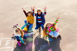Group of four boys and girls, friends in autumn clothes painting with chalk on the asphalt lifting hands with smile on theirs faces
