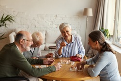 Group of four cheerful senior people, two men and two women, having fun sitting at table and playing bingo game in nursing home