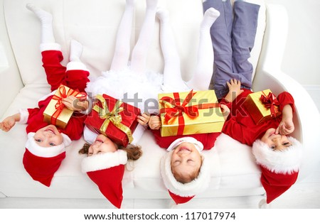 Group of four children in Christmas hat on sofa head over heels